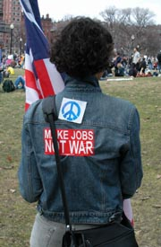 "Woman's back, wearing peace sign and ""Make Jobs, Not War"" sticker."